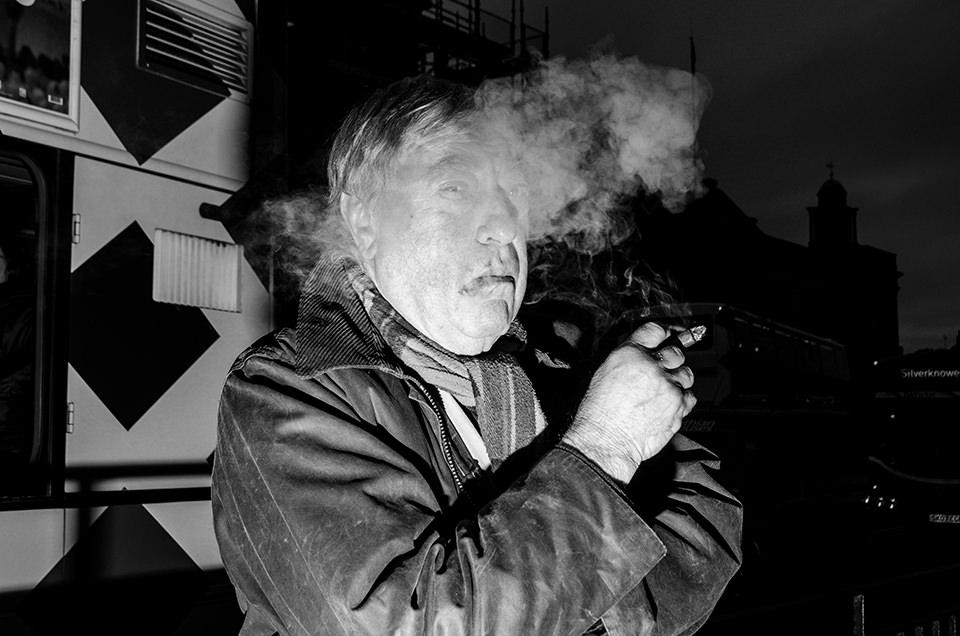 Eine Straßenfotografie zeigt einen rauchenden Senioren.