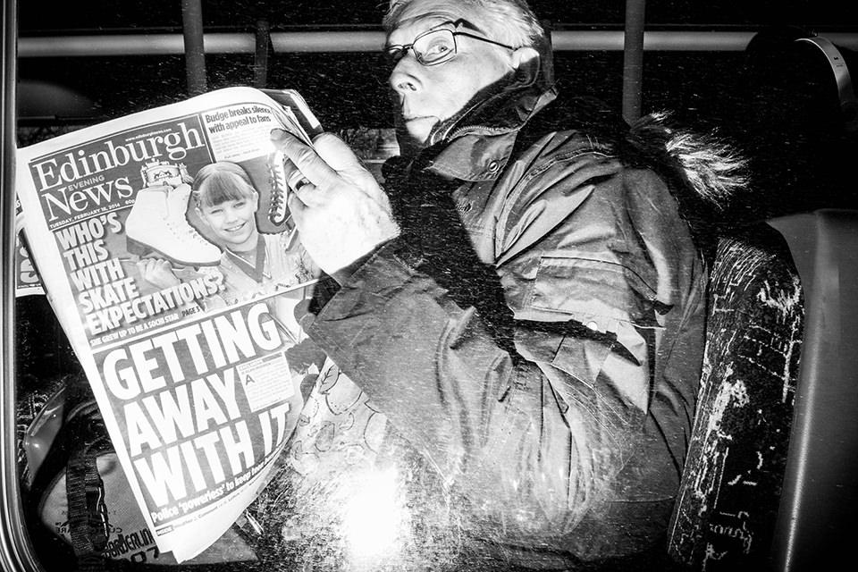 Eine Straßenfotografie zeigt einen Mann, der Zeitung liest.