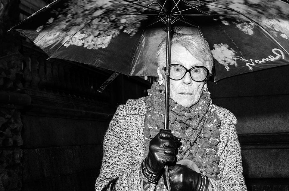 Eine Straßenfotografie zeigt eine Frau unter einem Schirm.