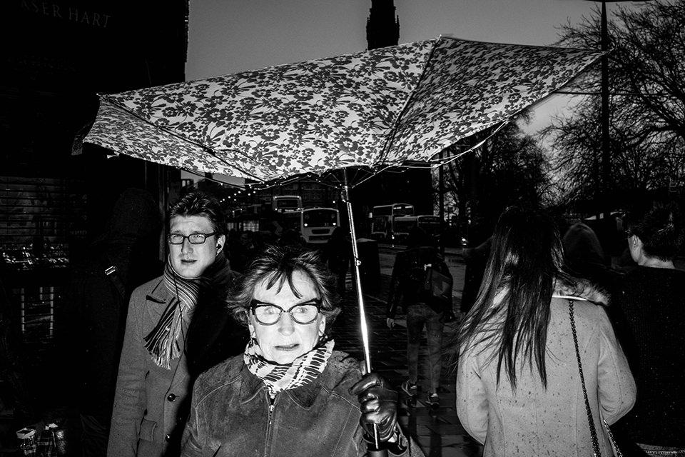 Eine Straßenfotografie zeigt eine Frau mit hochgewehtem Schirm.