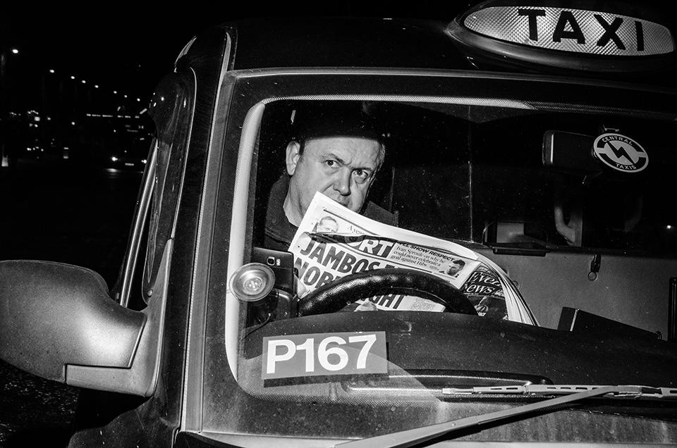 Eine Straßenfotografie, die einen Zeitung lesenden Mann zeigt.