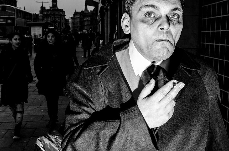 Eine Straßenfotografie zeigt einen rauchenden Mann.