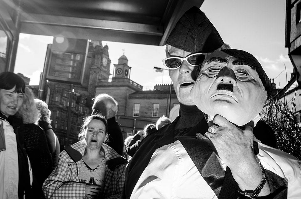 Eine Straßenfotografie mit einem Mann, der eine Hitler-Maske abnimmt.