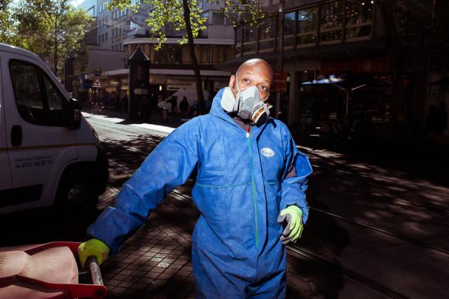 Straßenfotografie: Ein Arbeiter mit Maske und blauem Anzug.