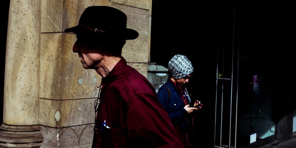 Straßenfotografie: Ein Mann mit Hut läuft vorbei.