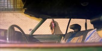 Eine Straßenfotografie, die eine Frau zeigt, die sich an eine Wand lehnt. Von Todd Gross.