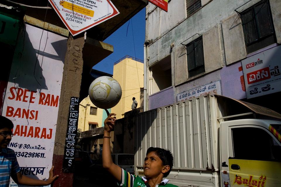 Ein Junge balanciert einen Ball auf der Straße.