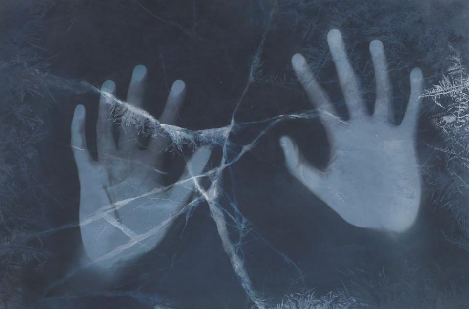 Hände drücken auf eine zersprungenen Fläche, die wie Eis wirkt.