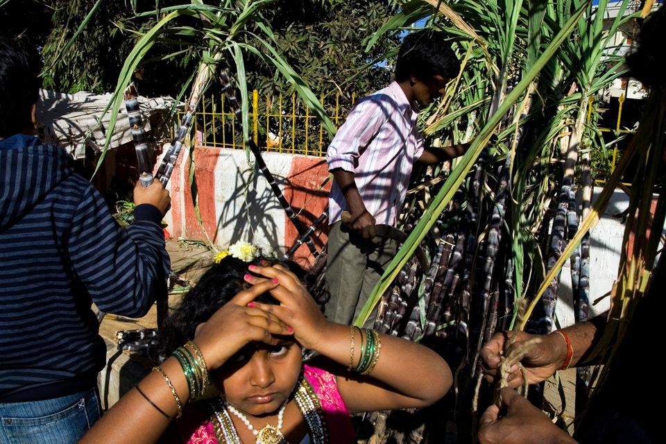 Eine Straßenfotografie mit einem Mädchen im Vordergrund, das sich die Hände an die Stirn hält.