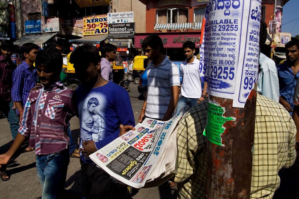 Eine Straßenaufnahme, bunt und mit Zeitungen im Vordergrund.