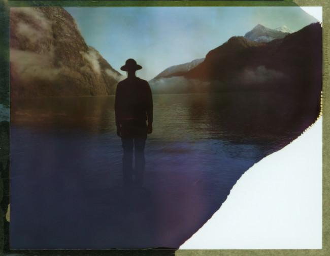 Ein Mann mit Hut steht an einem See.