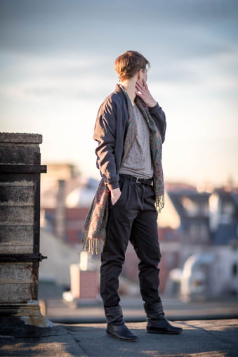 Eine junge Frau steht bei niedrigstehender Sonne auf einem Dach und schaut hinter sich über die Stadt.