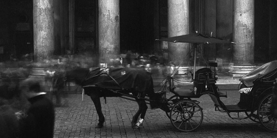 Wir sehen eine verwischte Menschenmenge und eine Pferdekutsche vor dem Portal des Pantheon in Rom.