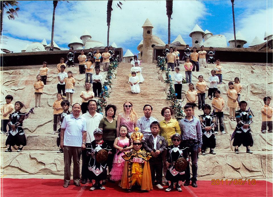 Eine Gruppe von Touristen lässt sich mit den kleinen Bewohnern des Parks fotografieren. Im Zentrum steht die Fotografin mit rosa Sonnenbrille.