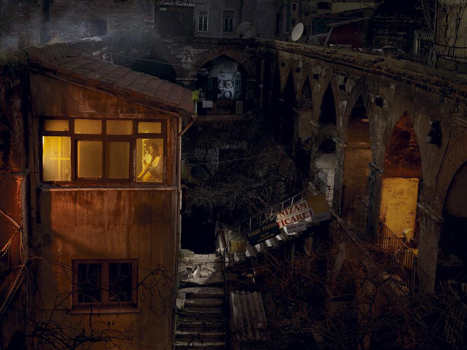 Eine Karawanserei. Blick auf Häuser, die durch Treppen miteinander verbunden sind. In einem hellerleuchteten Fenster sitzt eine Frau.