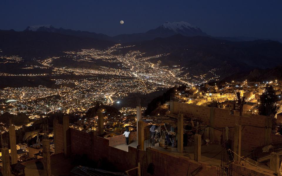 Nachtaufnahme. Im Vordergrund eine Frau, die von einer Aussichtsplattform auf die nächtlichen Lichter der Stadt blickt.