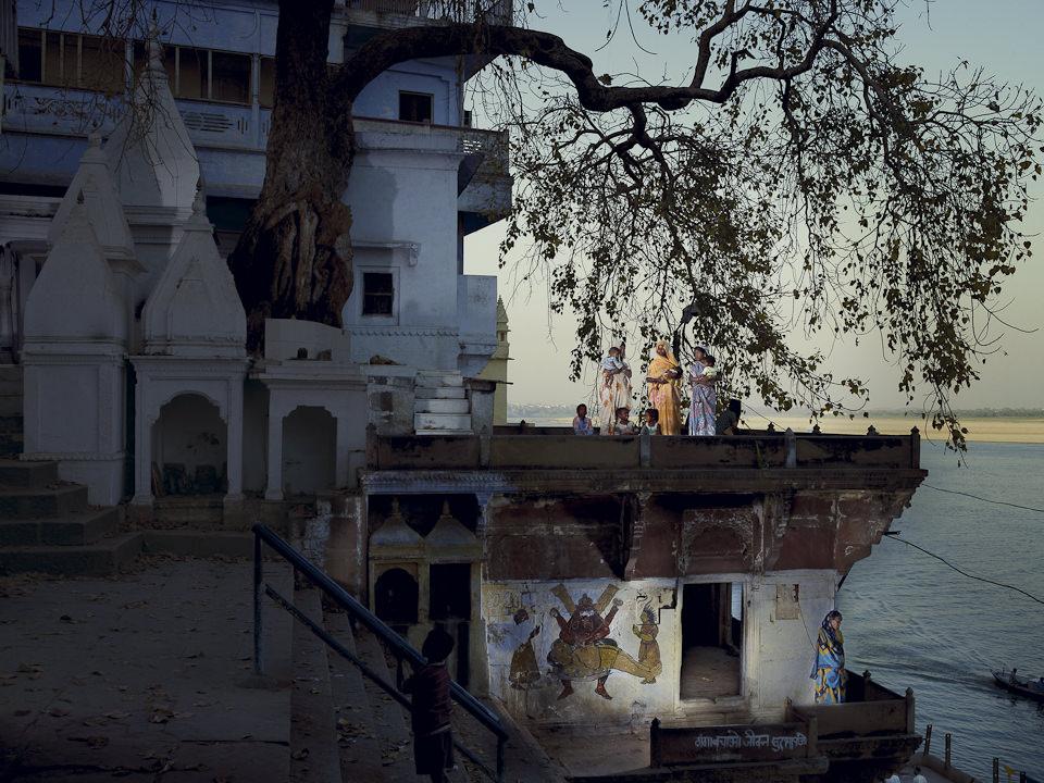 Frauen in bunten Gewändern stehen auf dem Dach eines Hauses.