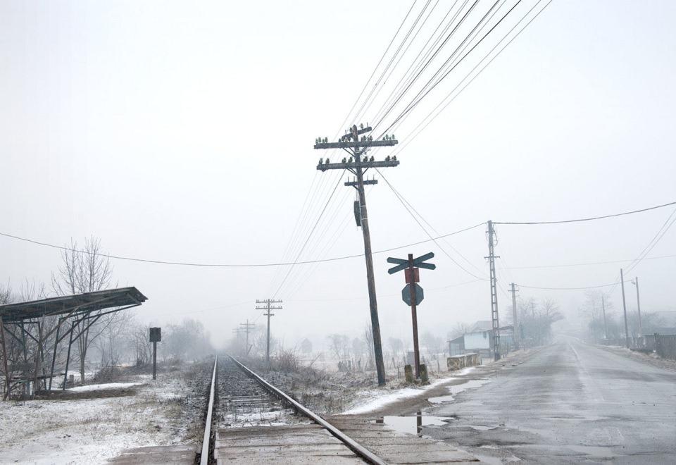 In einer nebligen, menschenleeren Schneelandschaft kreuzen sich eine Straße und Bahnschienen in einem spitzen Winkel.