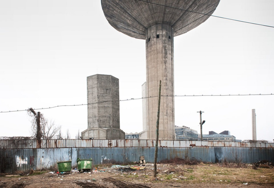 Industriebauten aus Beton, im Vordergrund ein hoher Zaun, Müllcontainer und Schrott.