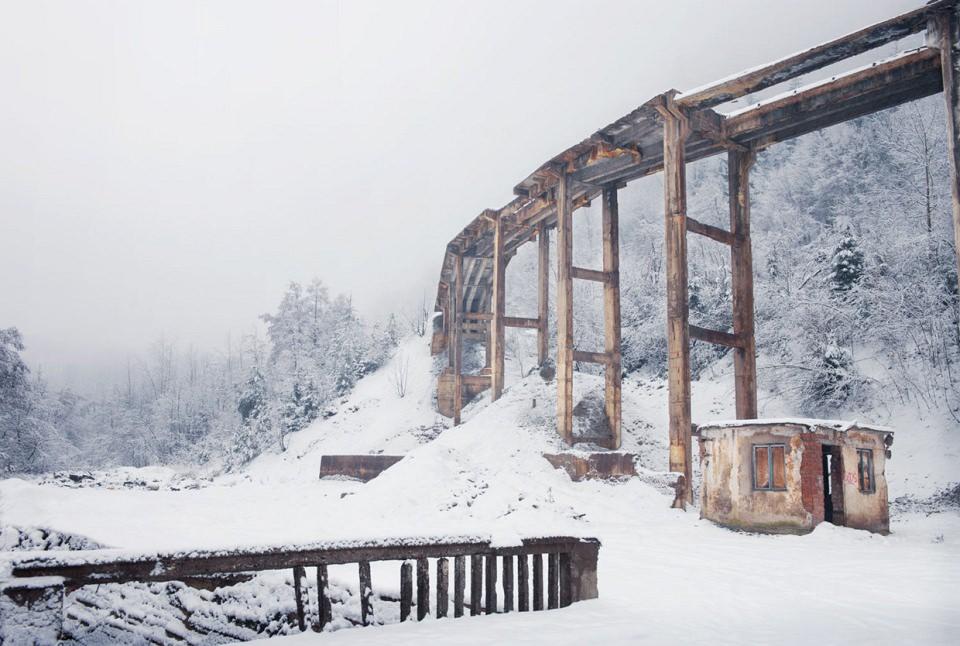Eine zerfallene Holzbrücke in einer Schneelandschaft.
