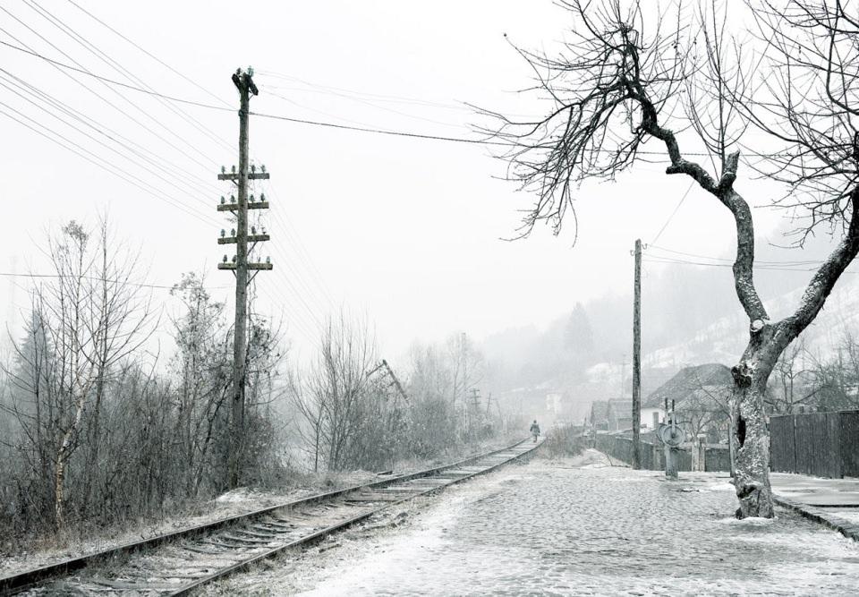 In einer Schneelandschaft stehen ein Baum und ein Telegrafenmast neben in die Ferne verlaufnden Bahngleisen, auf denen eine Person läuft.
