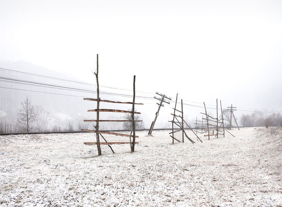 Gatterartige Holzkonstruktionen und ein schiefer Telegrafenmast in einer Schneelandschaft.