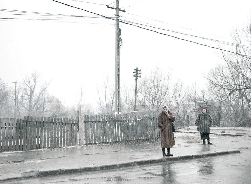 Zwei Frauen in Pelzmänteln stehen an einer verregneten, dörflichen Kreuzung.