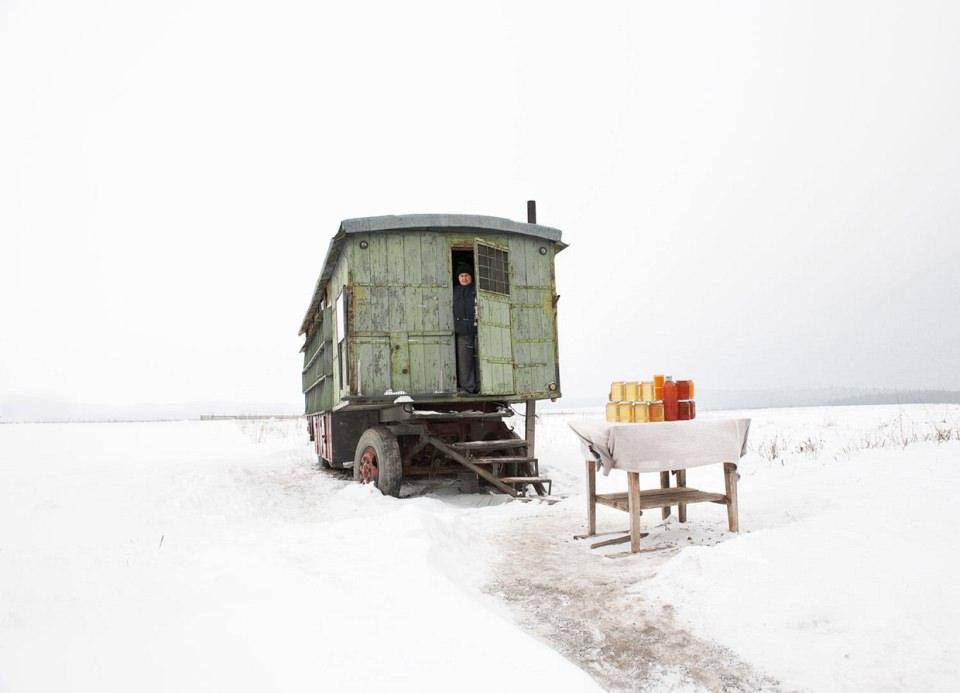 In einer weiten Schneelandschaft steht ein einsamer Bauwagen, aus dem ein Mann guckt, davor steht ein Tisch mit aufgetürmten Einweckgläsern.