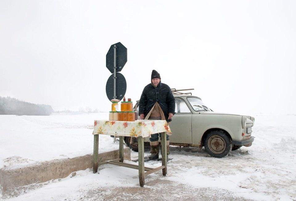 Ein Mann mit einem Tisch, auf dem Einweckgläser aufgetürmt sind, steht mit einem Trabbi an einem Straßenschild in einer weiten Schneelandschaft.