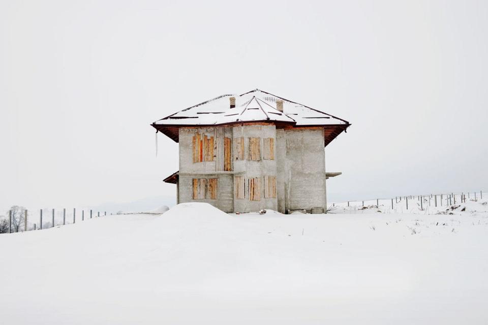 In einer weiten Schneelandschaft steht ein einzelnes Haus, dessen Fenster mit Holzbrettern vernagelt sind.