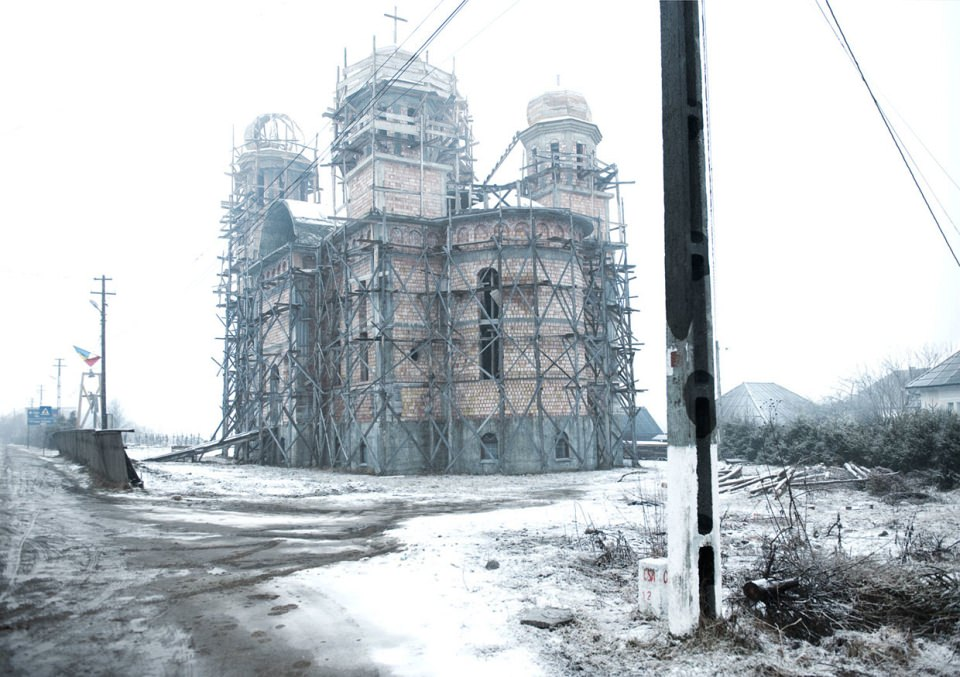 Eine alte Kirche, komplett in ein Baugerüst gehüllt, steht in einer trostlosen Schneelandschaft.