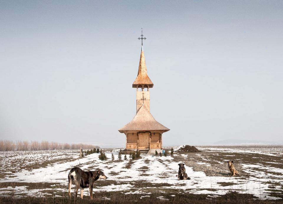 Weite Feldlandschaft mit etwas Schnee, in deren Mitte eine Holzkirche steht, im Vordergrund lungern drei Hunde herum.
