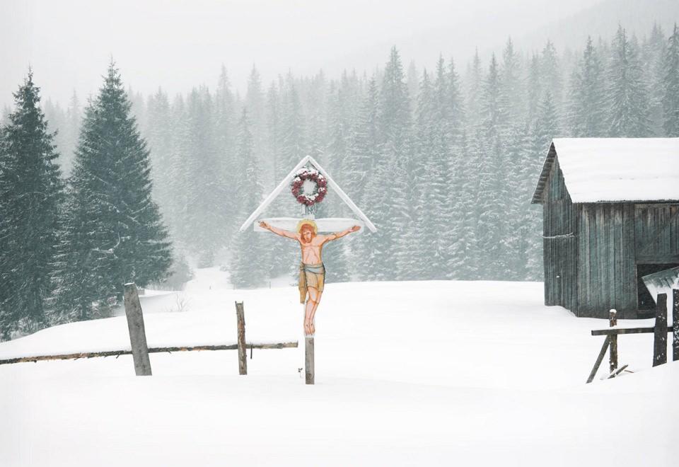 Vor einer schneebedeckten Nadelwaldkulisse steht ein weißes Holzkreuz, an dem eine naiv gemalte Jesusfigur hängt.