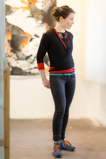 Eine junge Frau steht entspannt in einem Galerieraum und schaut nach rechts.