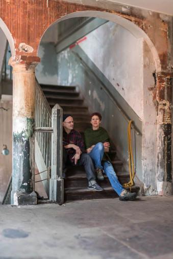 Ein Mann und eine Frau sitzen auf den Stufen einer Treppe in einem alten unrenovierten Gebäude.