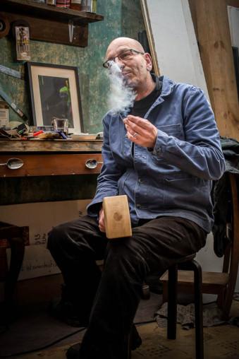 Ein Mann sitzt in seiner Werkstatt und raucht.