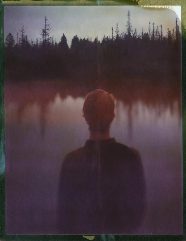 Eine Person steht vor einem See, von hinten fotografiert.