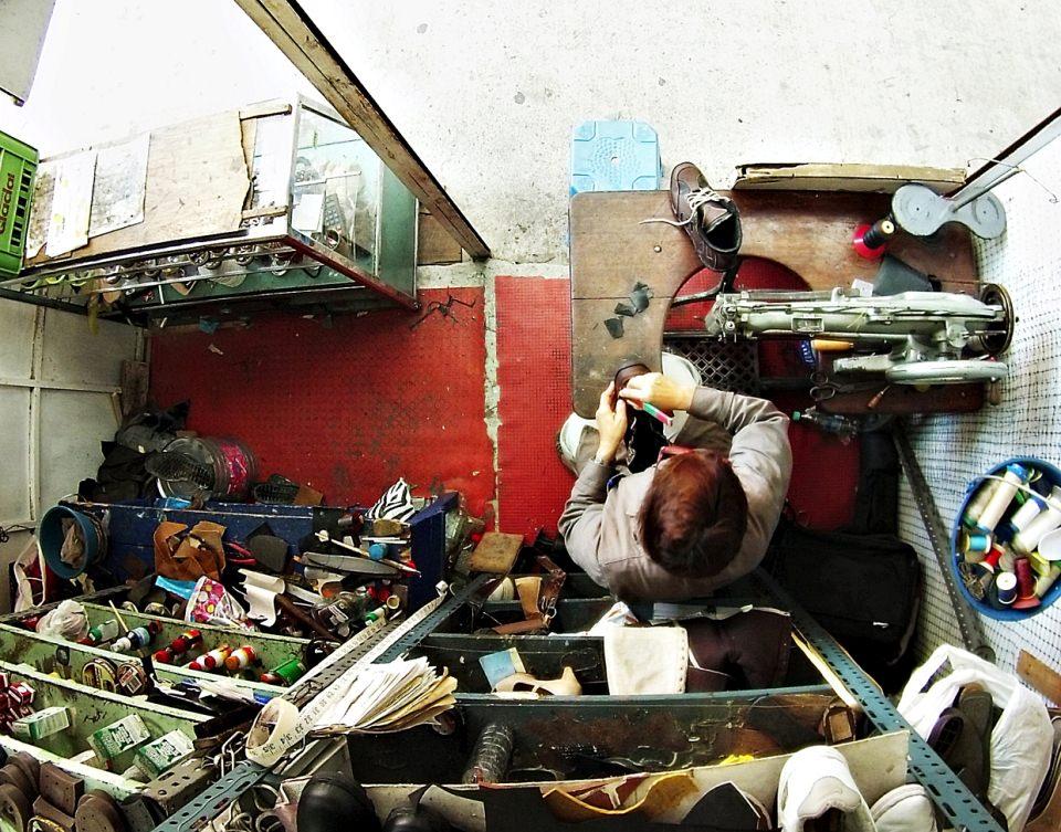 Winziges Ladengeschäft einer Schuhmacherin, weitwinklig von oben fotografiert.