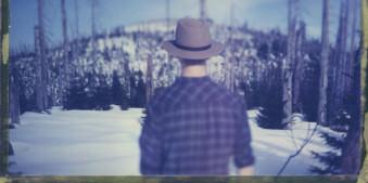 Ein Mann mit Hut steht vor einem gefrorenen Blockmeer.