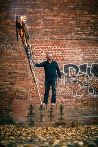 Ein Mann steht auf einem Stapel Kartons und hält eine überdimensionale brennende Fackel.