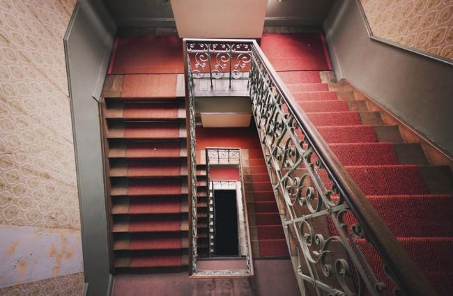 Blick auf ein Treppenhaus in einem verlassenen Gebäude.