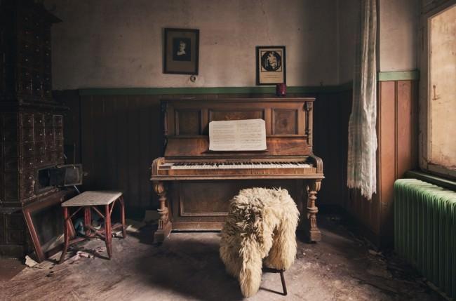 Ein Klavierzimmer mit Fensterlicht und einem Hocker, auf dem schon lange niemand mehr saß.