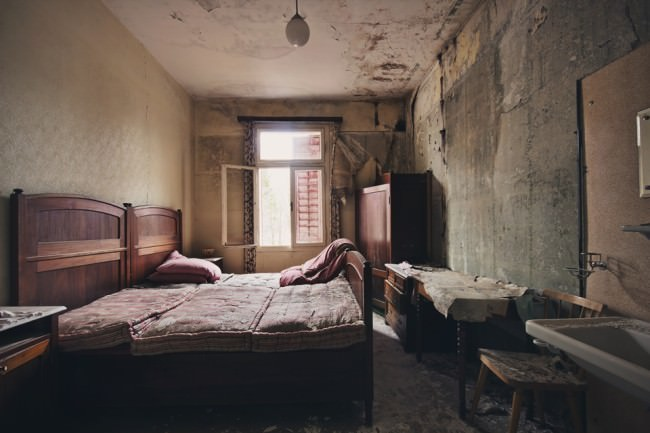 Die Reste eine Schlafzimmers in einem verlassenen Haus mit offenem Fenster.