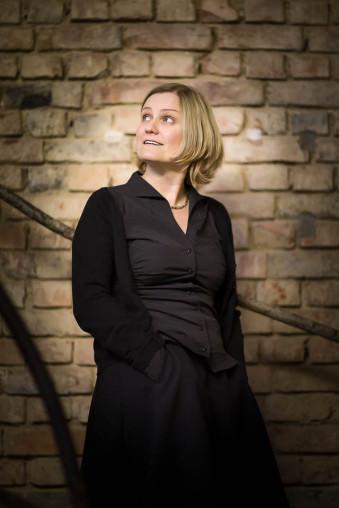 Eine Frau steht vor einer unverputzten Ziegelwand und schaut nach oben.