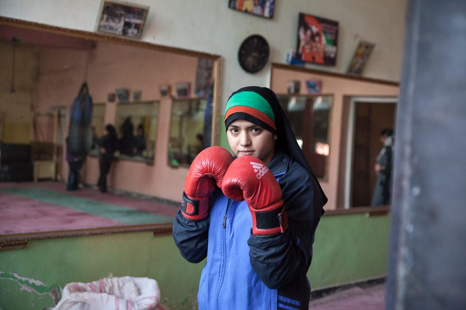 Eine junge Frau mit Kopftuch trägt Boxhandschuhe und hält diese in Pose zur Kamera.