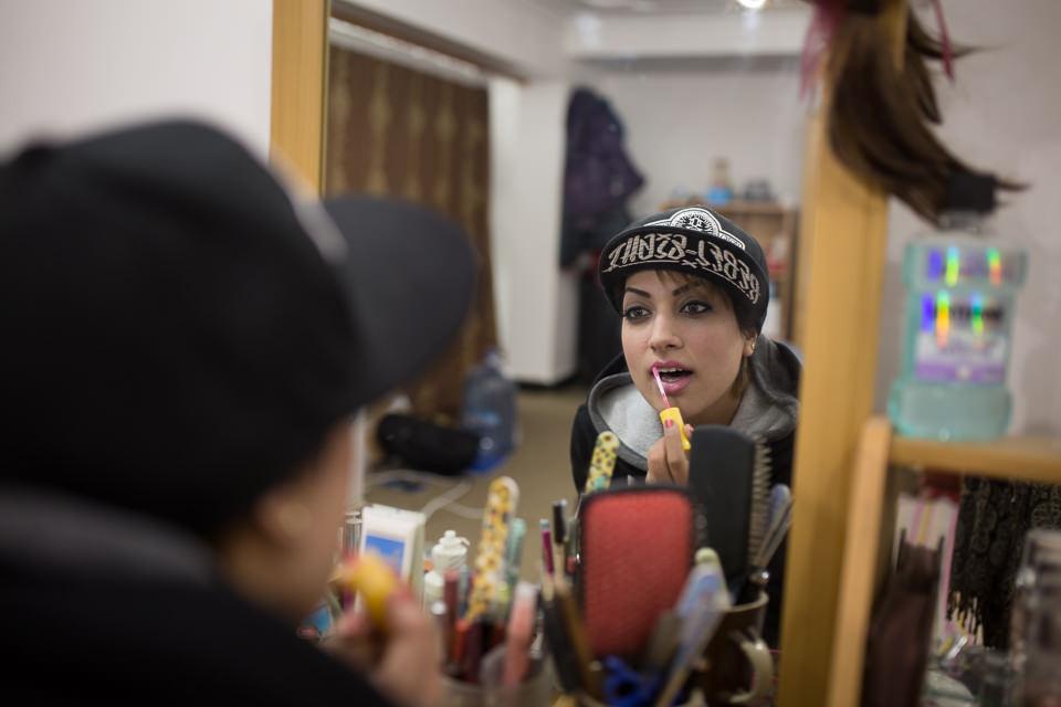 Eine junge Frau mit Baseballkappe trägt Lippenstift auf. Man sieht nur ihr Spiegelbild.