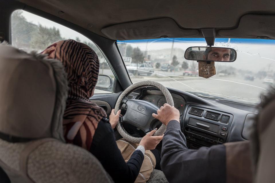 Eine Frau sitzt im Auto am Steuer. Der Fahrlehrer greift ihr gerade ins Lenkrad.
