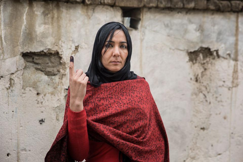 Eine Frau in rotem Umhang und schwarzem Kopftuch hällt ihren mit Tinte getränkten Zeigefinger nach oben.