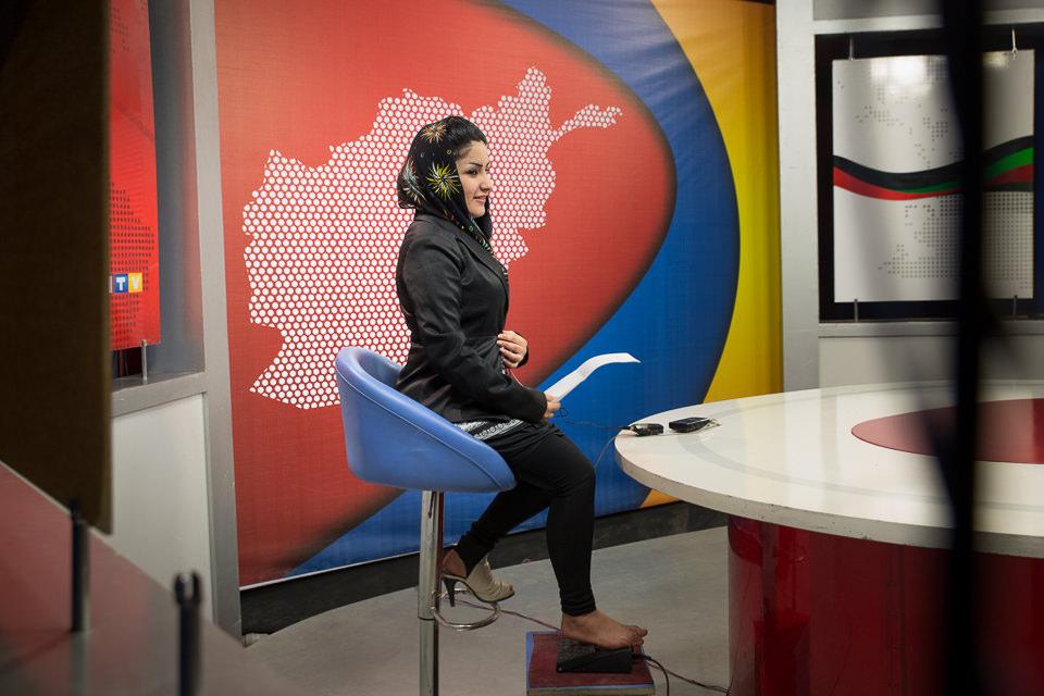 Eine junge Frau sitzt in einem Studio auf einem Stuhl.
