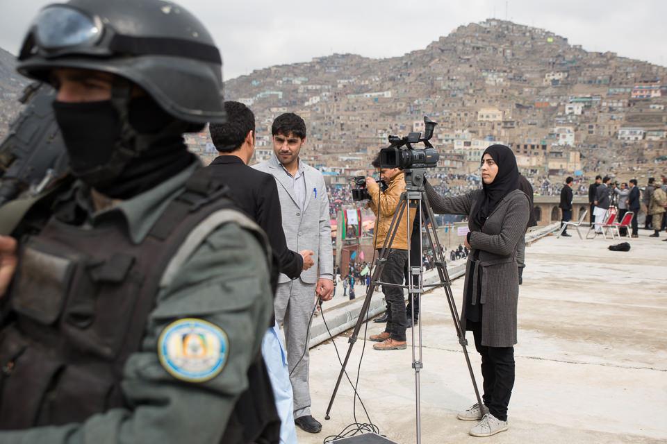 Eine Frau inmitten von Männern steht an einer Videokamera.